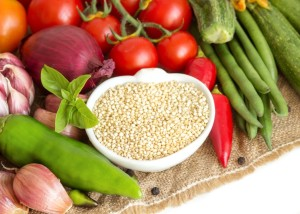 Raw organic quinoa in a bowl and vegetables